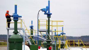 Työntekijä öljyputken pumppuasemalla