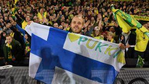 Teemu Pukki juhlii Norwichin nousua Suomen lipun kanssa.