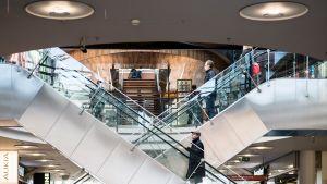 Ihmisiä rullaportaissa ostoskeskuksessa.