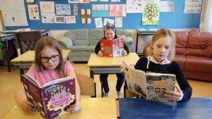 Svenska Skolanin oppilaat Peppi Johansson, Aada Johansson ja Maya Ikonen lukevat kirjoja luokkahuoneessa.