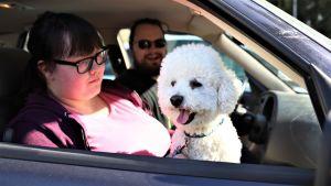 Saana Toikka ja Ossi Termonen istumassa autossa koiransa kanssa.