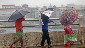 Ihmisiä ylittämässä Burigangajokea Dhakassa ankarassa sateessa.