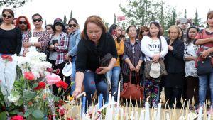 Joukko naisia sytyttämässä muistokynttilöitä.