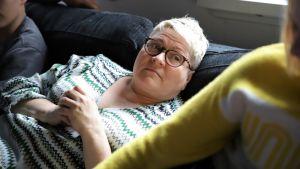Pallo-kotien toimitusjohtaja Sari Itäpelto makailee sohvalla nuorten kanssa