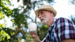 Eläkeläinen juo kahvia ulkona.