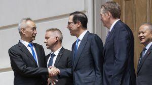 Kiinan ja Yhdysvaltojen neuvottelijat kättelevät toisiaan portaissa Washingtonissa.