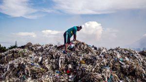 Mies lajittelee ulkomailta tuotua muovijätettä Indonesiassa.