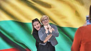 Ingrida Šimonyten vaalitilaisuudessa on riehakas tunnelma, kun kannattajat ja kampanjatyöntekijät ottavat kuvia suosikkinsa kanssa. Presidenttiehdokas Šimonyte on kuvassa oikealla.