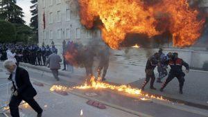 Poliisit yrittävät välttää mielenosoittajien heittämiä räjähtäviä pommeja Tiranassa, Albaniassa, 11. toukokuuta 2019. Opposition kansanedustajat ovat vaatineet pääministerin Edi Raman eroamista ja ennenaikaisia vaaleja.