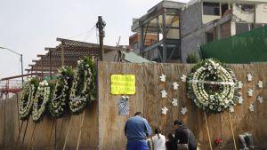 Mies, nainen ja kaksi lasta muistelemassa maanjäristyksessä menehtyneitä Rebsamen-koulun vieressä.