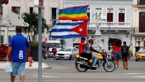 Moottoripyörän kyydissä istuva ihminen heiluttaa Kuubam lippua ja sateenkaarilippua.