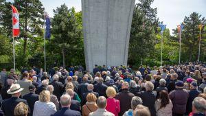 Taustalla muistomerkki. Edessä joukko muistojuhlaan kokoontuneita ihmisiä.