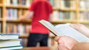 mies lukee pääsykokeisiin kirjastossa