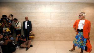 Kuvan oikeassa reunassa värikkääseen asuun pukeutunut kansanedustaja. Vasemmassa reunassa joukko valokuvaajia.