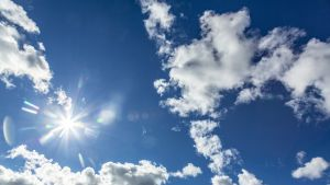 Sininen taivas aurinko ja pilviä.