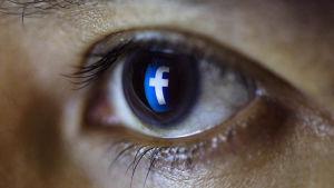 facebookin f -kirjain kiiluu ihmissilmässä.