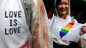 Nainen näyttää kuvaa sateenkaaren väreissä olevasta Taiwanin kartasta. Vasemmassa reunassa Love is love -teksti.