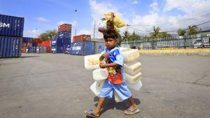 Pieni poika kantaa useita tyhjiä muovikanisteria.