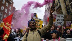 Joukko mielenosoittajia. Naisella kädessään vaaleanpunaista savua levittävä pakkaus.