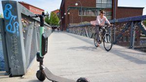 Sähköpotkulauta pysäköitynä Tampereen Patosillalle, kuvassa myös pyöräilijä.