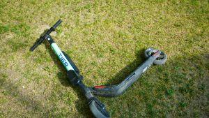 Turkoosi sähköpotkulauta kyljellään nurmikolla.