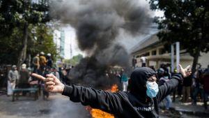Kasvonsa peittänyt mielenosoittaja taustallaan liekkejä ja savua.