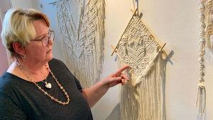 Nainen osoittaa seinällä olevaa makramee-työtä.