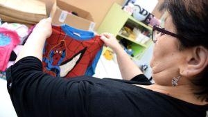 Nainen tutkii lahjoitukseen tulleita lastenvaatteita