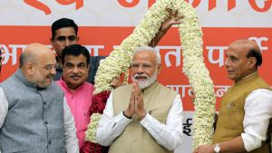 Pääministeri Narendra Modi seisoo puoluetovereidensa ympäröimänä. Taustalla suuri kukkaköynnös.