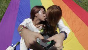 Kaksi naista suutelee sateenkaarilipun päällä.