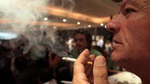 Mies polttaa tupakkaa. Iso savupilvi.