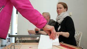 Henkilö laittaa äänestyslippua vaaliuurnaan.