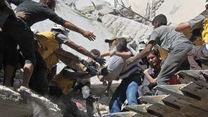 Vapaaehtoiset auttoivat lapsen ulos pommitetun rakennuksen raunioista maanantaina Arihan kaupungissa Idlibin maakunnassa. Ainakin yhdeksän ihmisen kerrotaan kuolleen maanantain pommituksissa.