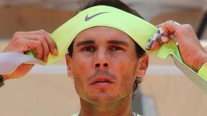 Rafael Nadal sitoo vihreää pantaa päähänsä