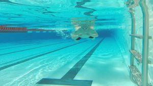 Mies kuvattuna veden alla uimassa