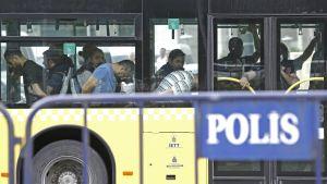Pidätettyjä miehiä istuu bussin kyydissä.