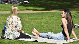 Ihmiset viettivät lämmintä ja aurinkoista päivää Vanhassa kirkkopuistossa Helsingissä 19. toukokuuta.