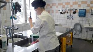 Kokkiopiskelija pesee astioita ammattikoulun harjoittelukeittiössä.