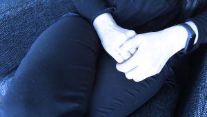 Nainen istuu kädet sylissään.