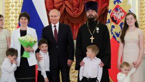 Vladimir Putin ympärillään lapsia, nainen ja pappi.