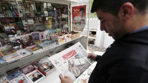 Mies tutkii iranilaista sanomalehteä kioskin edustalla Teheranissa.