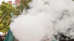 Naisen pää peittynyt kannabiksen savuun.