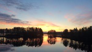 Maisemakuva järven rannasta ennen auringonnousua.
