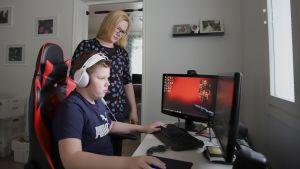 Elina Kehusmaa ja poika Jonne pelaamassa tietokoneella.