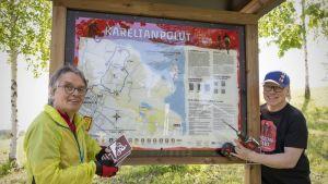 Ilpo Jorasmaa ja Vesa Turtia upouuden Karelianpolut-kyltin äärellä.