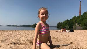 Seelia Rahkola tekee spagaatin uimarannalla.