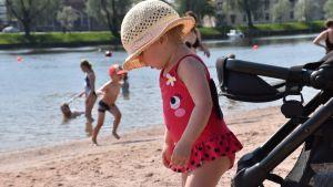Pieni tyttö hellehattu päässä uimarannalla.