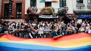 Sateenkaarilippu ja suuri ihmisjoukko Stonewall Innin edessä.