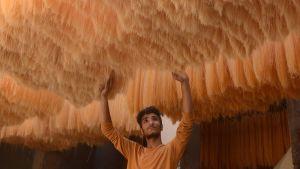 Mies tarkistaa Itä-Pakistanilaisessa tehtaassa nuudelien kuivumista Lahoressa.