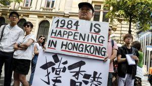 """Berliinissä mielenosoittajan kyltissä luki """"1984 tapahtuu Hongkongissa"""". Kyltti viitannee George Orwellin 1984 -romaaniin, joka kuvaa kaikkea valvovaa yhteiskuntaa."""